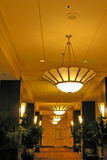 Hotel Hall. Way with chandeliers, and sconces on pillars, exit sign in background Royalty Free Stock Photos