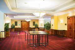 Hotel hall. Inside of a hotel hall with red carpet and tables placed in the center Stock Photos