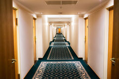 Hotel hallway. Perspective of a hotel hallway with room doors and warm light Stock Images