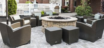 Fire pit surrounded by chairs on a patio royalty free stock photos
