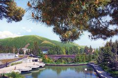 Hotel Hyatt Place Jermuk. View of Dolphin lake, mountains, bridge, sky and pine branches. Armenia.  Stock Photo