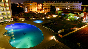 Hotel with illuminated swimming pool at night Stock Photo