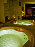 Hotel jacuzzi. Elegantly lit with candles and green light, sauna reflected in the mirror Stock Photography