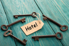 Hotel key with tag on the wooden background. VIntage hotel key with tag on the wooden background Stock Photography