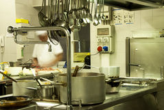 Hotel kitchen. Modern kitchen in a hotel or restaurant, The chef is in movement and so he is out of focus and unrecognizable royalty free stock photography