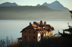Hotel on lake shore. Lake and mountains in the background Royalty Free Stock Photos