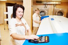 Hotel linen service. Hotel linen cleaning services. Woman with ironing machine working Royalty Free Stock Images