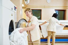 Hotel linen washing service. Hotel linen cleaning services. Woman operating with industrial washing machine Royalty Free Stock Photography