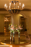 Hotel lobby with chandelier and flowers. Fancy hotel lobby with chandelier, and flowers in vases on a table Royalty Free Stock Images
