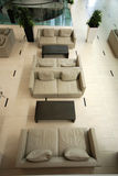 Hotel lobby in contemporary style. Contemporary lobby area from above with modern furniture, beige sofas and tile floor in luxury hotel Royalty Free Stock Images