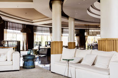 Hotel Lobby Interior Design. Fragment of the lobby of the five stars luxury hotel. Lounge area. Interior design. white chairs and sofas and vintage table Stock Image