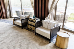 Hotel Lobby Interior Design. Fragment of the lobby of the five stars luxury hotel. Lounge area. Interior design. white chairs and sofas and vintage table Royalty Free Stock Photography