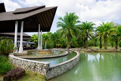 Hotel lobby in Thailand with swimming pool and fountain. Stone pond with fountain near the large roof in the hotel against the jungle and palm trees stock image