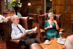 Hotel lounge area with senior couples Stock Photo