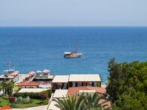 Hotel lujoso, palmas, piscina y una nave en el mar Fotos de archivo