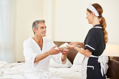 Hotel maid bringing slippers for guest Stock Images