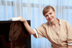 Hotel maid dusting furniture Royalty Free Stock Images