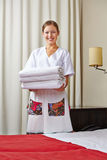 Hotel maid with fresh towels Stock Photos