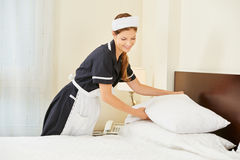Hotel maid making bed in hotel room. During house keeping Stock Photos