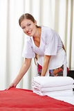 Hotel maid making bed in hotel room. Smiling hotel maid making the bed in a hotel room Stock Photo