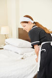 Hotel maid making bed during housekeeping. In hotel room Royalty Free Stock Image
