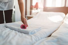 Hotel maid making a bed. And putting flower on towel Royalty Free Stock Images