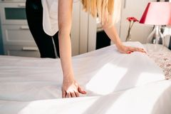 Hotel maid making a room bed Stock Images
