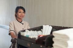 Hotel maid. Pretty young Vietnamese maid with housekeeping cart going to clean rooms royalty free stock photo