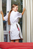 Hotel maid pulling up curtains Royalty Free Stock Photography