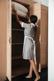 Hotel maid putting bed pillows in a closet. Full length rear view of a hotel maid putting bed pillows in a closet royalty free stock images