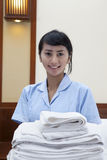 Hotel maid with towels posing in a hotel room Royalty Free Stock Photography