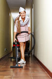 Hotel maid with vacuum cleaner in corridor Stock Photography