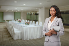 Hotel manager. Lovely hotel manager standing in banquet hall royalty free stock photography