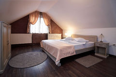 Hotel mansard bedroom. Interior view of a rustic hotel mansard bedroom Stock Images