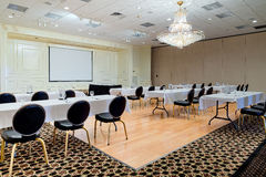 Hotel Meeting Event Room. Empty hotel conference meeting or event room provides space for business meetings, conferences, speakers, or events. Tables and chairs Stock Image