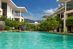 Hotel met hemel-blauw zwembad met palmen Royalty-vrije Stock Afbeeldingen