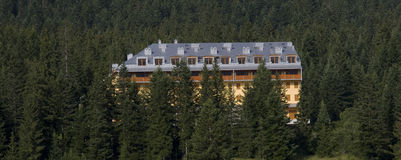 Hotel in the mountains. A panoramic view of a hotel in the mountain woods Royalty Free Stock Image