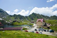 Hotel between mountains in Romania. Scenic view of a hotel in Romania at Balea Lake in Fagaras mountains. Holiday and tourism concept. Landscape with blue sky Royalty Free Stock Photos