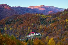 Hotel in the mountains. Surrounded by colorful forests in the fall Stock Photos