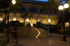 Hotel at night. Picture of a pretty hotel at night time with palms and stair on the front area Royalty Free Stock Photography