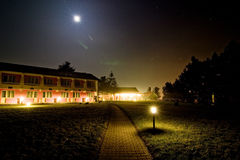 Hotel at Night. Night scene of hotel with spotlights on lawn around perimeter and walkway, under full moon and stars Stock Image