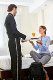 Hotel page bringing drinks as room service Stock Photography