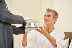 Hotel page bringing food as room service. To an elderly men in a hotel room Stock Images