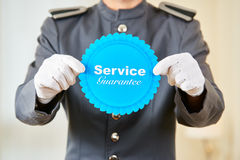 Hotel page holding service guarantee badge. In his hands Royalty Free Stock Photography