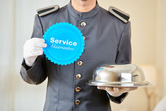 Hotel page holding service guarantee sign. And food under cloche Stock Images