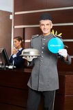 Hotel page holding Willkommen sign Stock Image