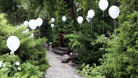 Hotel park in greenery decorated with white helium balls for celebration stock footage