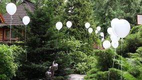 Hotel park in greenery decorated with white helium balls for celebration stock video