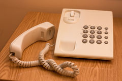 Hotel phone hanged off. A hotel phone sitting on a bedside table in a 3 stars hotel in East Europe royalty free stock images