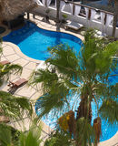 Hotel pool. A hotel pool with sparkling blue water and pool chairs for sunbathers Stock Images